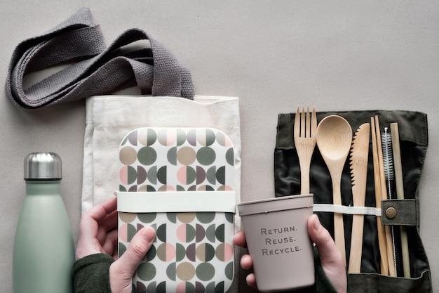 Kreative draufsicht, abfallfreies lunch-konzept, lunchbox zum mitnehmen mit bambusbesteck, wiederverwendbare box, baumwolltasche und hand mit kaffee zum mitnehmen oben auf bastelpapier. nachhaltiger lebensstil.
