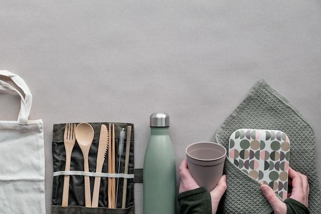 Kreative draufsicht, abfallfreies lunch-konzept ohne abfall, lunchbox zum mitnehmen mit bambusbesteck, wiederverwendbare box, baumwolltasche und hand mit kaffee zum mitnehmen oben auf braunem papier. nachhaltiger lebensstil.