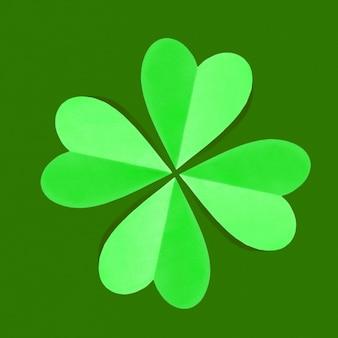 Kreative feiertagszusammensetzung aus handgemachten grünen kleeblattblättern des papiers auf einem grün mit kopienraum.