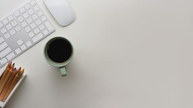Kreative flache arbeitsfläche mit computertastatur, maus, kaffeetasse und buntstiften auf dem tisch