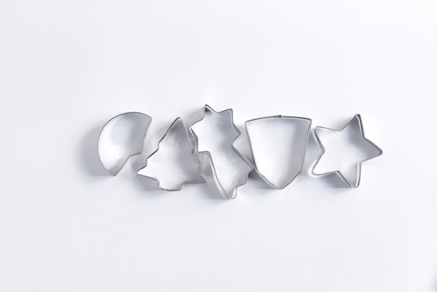 Kreative flache lage der dekorativen metall-ausstechformen zum kochen von hausgemachtem weihnachtsgebäck auf weiß
