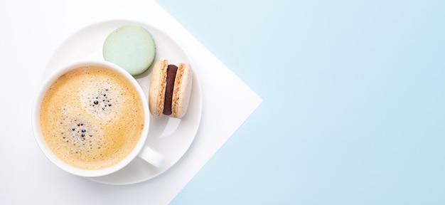 Kreative flache lage. tasse kaffee, verschiedene macarons auf blauem hintergrund. langes horizontales banner - image