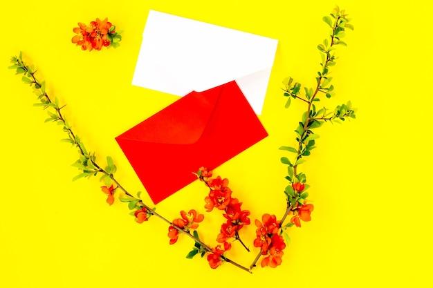 Kreative flache lage von leeren umschlägen rahmen mock-up und quittenbaumblütenblätter auf gelbem hintergrund mit kopienraum im minimalistischen stil, vorlage für schrift, text oder ihr design.