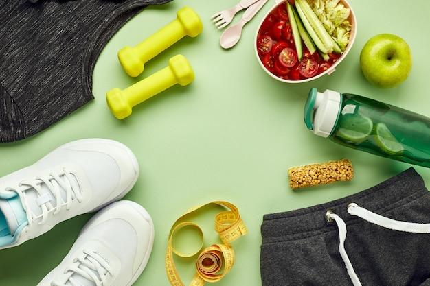 Kreative flache lage von sport- und fitnessgeräten. weiße turnschuhe für frauen, wasserflasche, sportbekleidung, hanteln und brotdose mit gesundem gemüsesalat