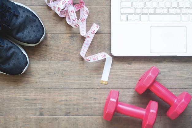 Kreative flache lage von sportausrüstungen und maßband mit laptop auf holzboden, diät und fitness-konzept