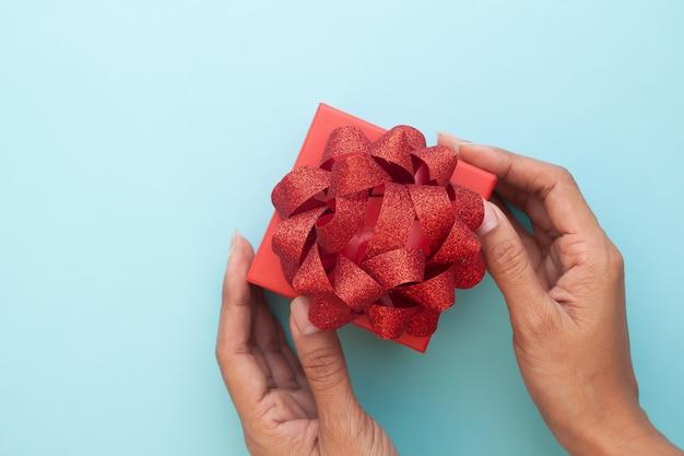 Kreative flache lagefrauenhand, die schöne rote geschenkbox auf pastellfarbhintergrund hält