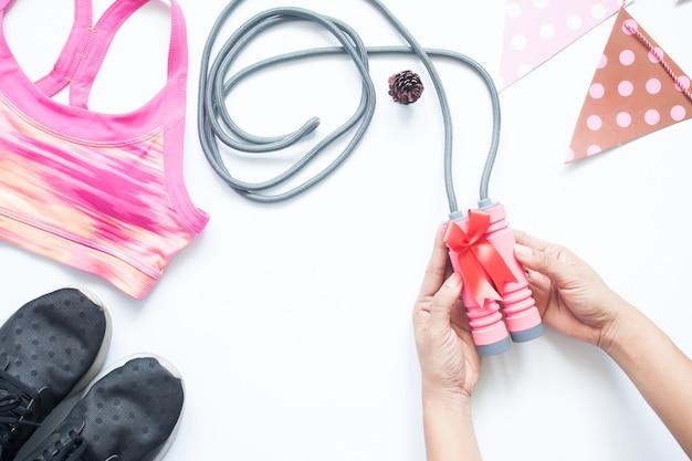 Kreative flache laien der frau hände geben geschenk mit sportartikel und ausrüstungen, gesunder lebensstil, geschenk für die gesundheit