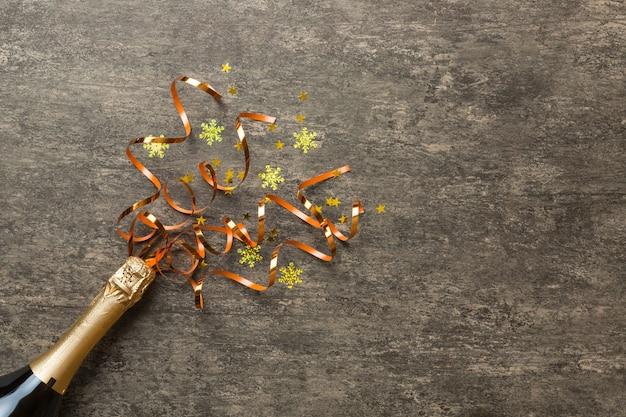 Kreative flache laienkomposition mit einer flasche champagner und platz für text auf farbigem hintergrund. sektflasche mit bunten partyschlangen. urlaubs- oder weihnachtskonzept
