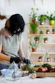 Kreative floristenfrau, die sukkulente in glasflorarium mit boden und steinen verpflanzt