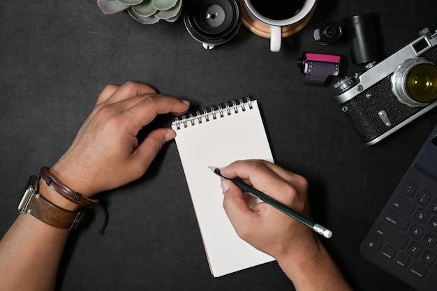 Kreative fotografschreibensanmerkung mit notizbuch auf schreibtisch