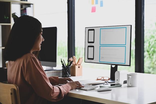 Kreative frau der seitenansicht, die im modernen büro arbeitet.