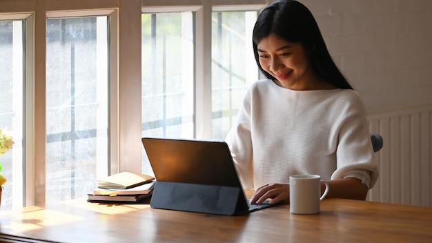 Kreative frau, die auf einem computertablett verwendet / tippt, während sie vor einer topfpflanze und büchern am modernen holztisch mit bequemem wohnzimmer und fenstern als sitzt