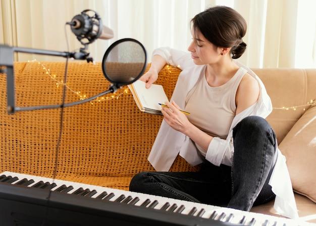 Kreative frau, die ein lied zu hause übt