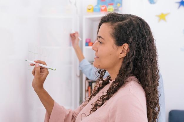 Kreative frau, die einen brainstorm auf whiteboard tut