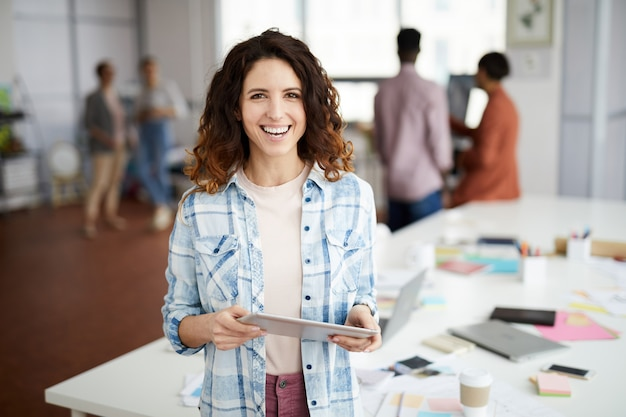 Kreative frau, die im büro lächelt