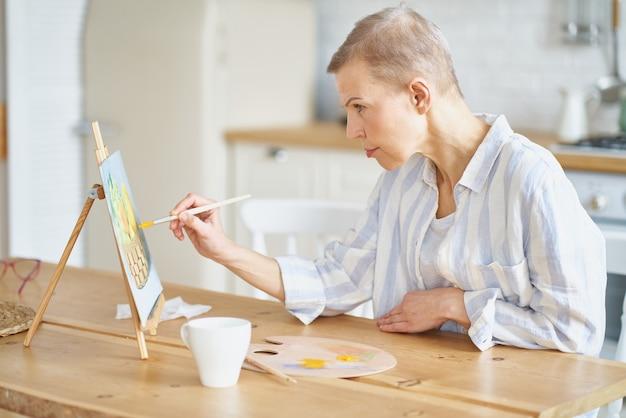 Kreative frau mittleren alters, die zu hause ein bild malt, während sie am holztisch in der küche sitzt