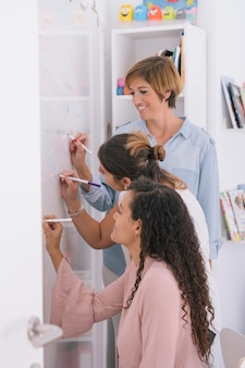 Kreative frauen, die einen brainstorming auf whiteboard tun