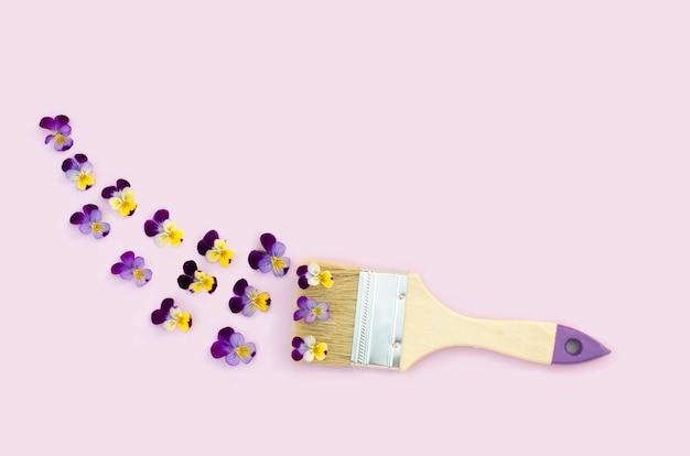 Kreative frühlings-, sommerblumenkomposition mit pinsel und stiefmütterchen auf rosa hintergrund