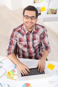 Kreative führungskraft. draufsicht auf einen gutaussehenden jungen mann mit brille, der am computer arbeitet und in die kamera lächelt, während er an seinem arbeitsplatz sitzt