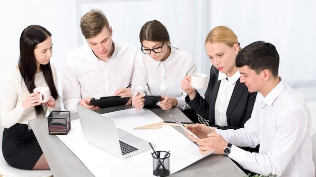 Kreative geschäftsleute mit handy; laptop und digitale tablette, die im büro zusammenarbeiten
