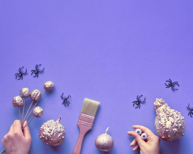 Kreative halloween-ebene lag hintergrund in lila, rosa, kopierraum. dekorative kürbisse, hände, pinsel und monster mit schokoladenaugen. diy dekorationen machen. quadratische komposition mit kopierraum.