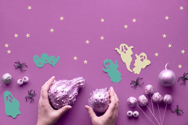 Kreative halloween-wohnung lag auf lebendiger rosa papierwand mit papiergeistern, sternen und schokoladenaugen. hände in schwarzen handschuhen halten kürbisse, die rosa vergoldet sind.