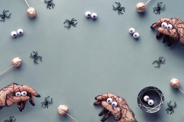 Kreative halloween-wohnung lag in grau, rosa und schwarz mit dekorativen kürbissen und spinnen. hände in schwarzen netzhandschuhen imitieren monster. grauer papier-halloween-hintergrund mit kopierraum