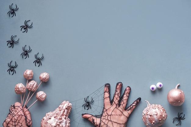 Kreative halloween-wohnung lag in rosa grau mit händen und metallischen kürbissen