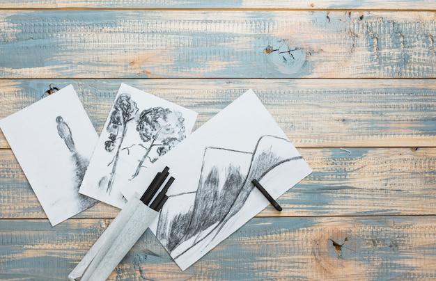 Kreative hand gezeichnete skizzen und holzkohlenstöcke über hölzernem schreibtisch