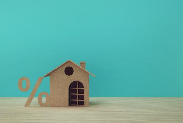 Kreative idee der hausmodellpapier- und -prozentsatzzeichensymbolikone auf holztisch. immobilieninvestitionen und hypothekenfinanzierungen.