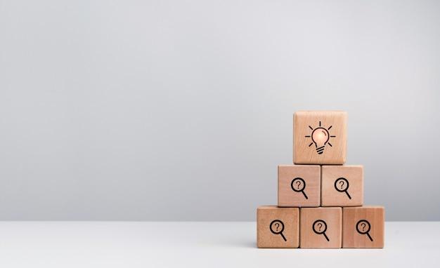 Kreative idee und problemlösungskonzept. glühbirnensymbol auf problemsymbol, suche und fragezeichen auf holzwürfelblock-stapelpyramide auf weißem hintergrund mit kopienraum.