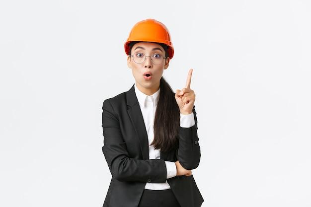 Kreative, intelligente asiatische bauingenieurin hat eine großartige idee, steht in schutzhelm, anzug, hebt den zeigefinger, sagt gedanken oder vorschlag, hat eine lösung gefunden, teilt ihren plan, weißer hintergrund