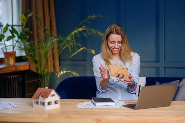 Kreative junge frau, desgner, die auf idee für neues projekt des 3d-modellhauses denkt.