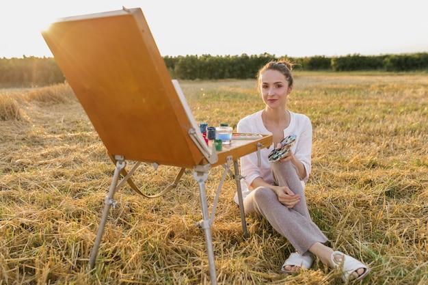 Kreative junge frau, die in der natur sitzt