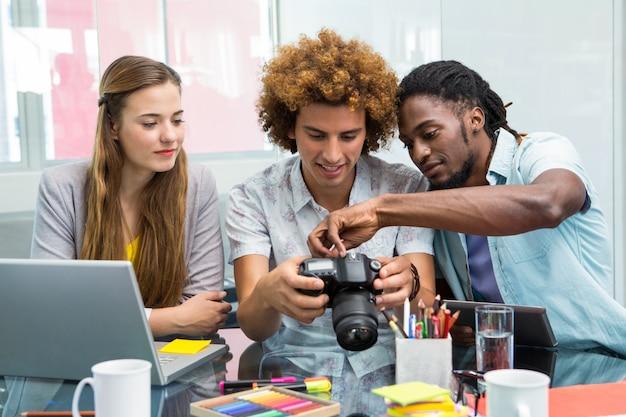 Kreative junge geschäftsleute, die digitalkamera betrachten