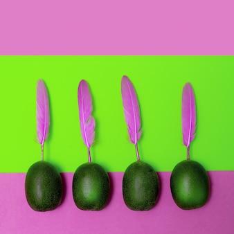 Kreative kiwi mit federn. minimale candy flat lay art