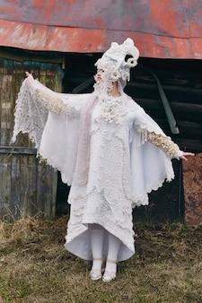 Kreative kleidung der neuen ethnischen russischen mode vogue des mädchens wirft nahe altem haus, weißem kleid und hut auf