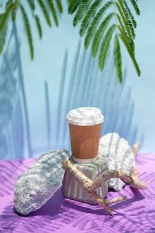 Kreative komposition aus braunem kraftpapier zum mitnehmen kaffeetasse auf naturstein podiumblau und lila...