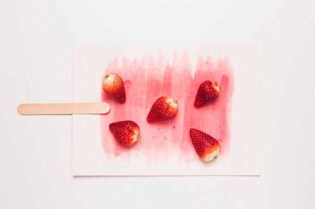 Kreative komposition aus eis am stiel aus duftenden erdbeeren am stiel