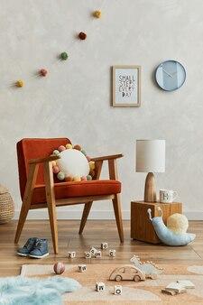 Kreative komposition aus gemütlichem skandinavischen kinderzimmer mit mock-up-posterrahmen, rotem sessel, plüschtieren und hängenden dekorationen. kreative wand. vorlage.