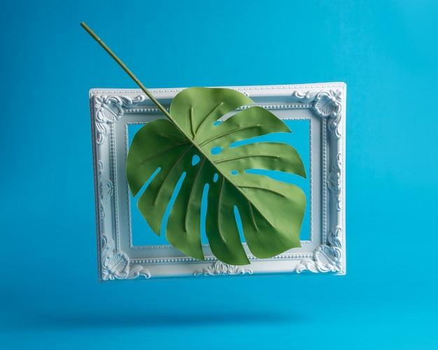 Kreative komposition aus palmblatt mit vintage-rahmen.