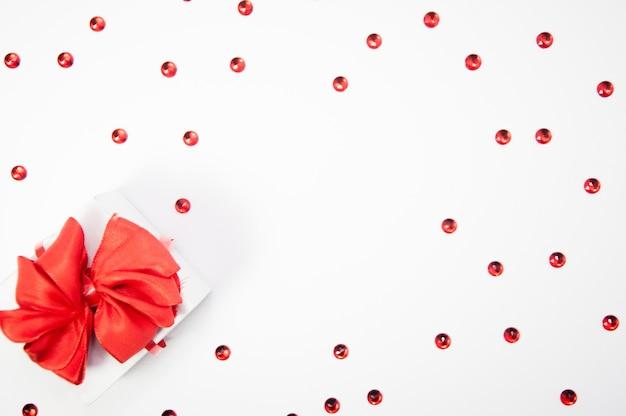 Kreative komposition aus roten kristallen und weißer geschenkbox mit rotem band auf weißem hintergrund mit kopienraum, glücklicher valentinstag, muttertag, flache lage, draufsicht