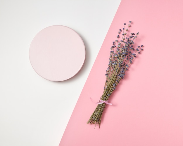 Kreative komposition aus rundem brett und natürlichem lavendelblütenzweig auf einem duotonen hellgrauen rosa mit kopierraum.