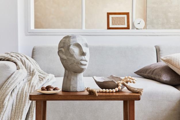 Kreative komposition aus stilvollem und gemütlichem wohnzimmerdekor mit mock-up-posterrahmen, grauem sofa, couchtisch, skulptur und persönlichen accessoires. beige neutrale farben. einzelheiten. vorlage.