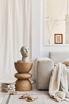 Kreative komposition aus stilvollem und gemütlichem wohnzimmerdekor mit mock-up-posterrahmen, grauem sofa, gestaltetem couchtisch, skulptur und persönlichen accessoires. beige neutrale farben. einzelheiten. vorlage.