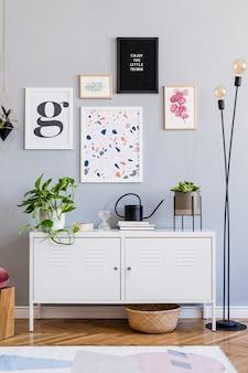 Kreative komposition aus stilvollem wohnzimmerdesign mit posterrahmen, weißer kommode, pflanzen und accessoires. modernes skandinavisches konzept. neutrale wände, parkettboden.