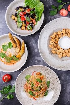 Kreative komposition. dekorierter tisch mit fertiggerichten, snacks. gebackener tomaten- und auberginensalat, hummus, gebratene knödel, funchose und gemüsesalat.