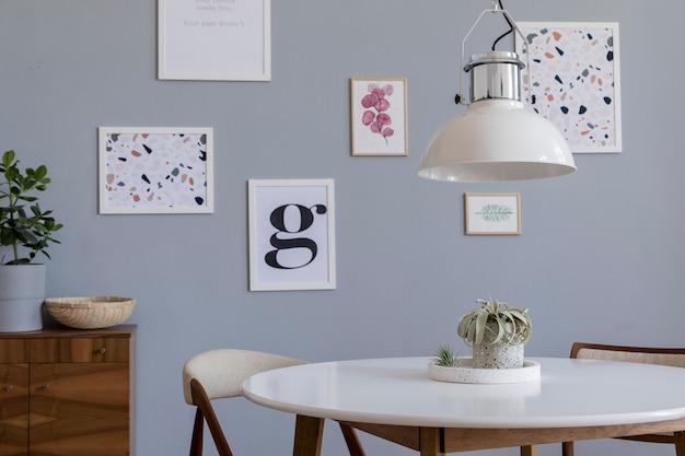 Kreative komposition der stilvollen skandinavischen wohnzimmereinrichtung mit posterrahmen, sofa, holzkommode, stuhl, pflanzen und accessoires. neutrale wände, parkettboden.