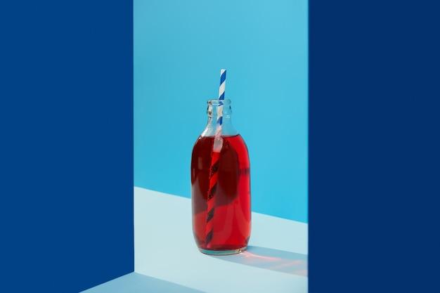 Kreative komposition des dunklen und hellblauen hintergrunds mit cranberrie-limonade-cocktail in der flasche