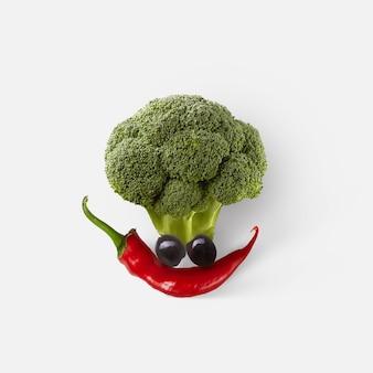 Kreative komposition in form eines lustigen gesichts aus frisch gepflücktem natürlichem bio-gemüse auf weißem hintergrund, kopierraum. veganes gesundes lebensmittelkonzept.